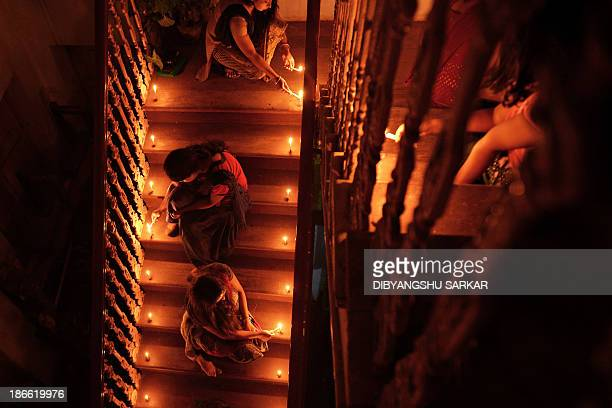 Family members light candles along a residential staircase on the eve of Diwali in Kolkata on November 2 2013 India is celebrating Diwali the...