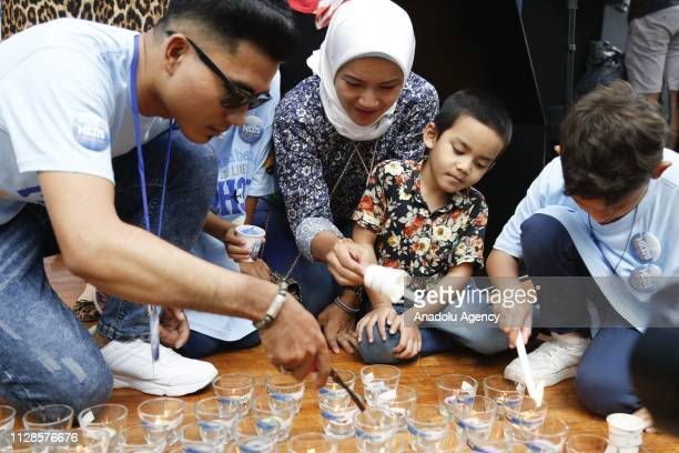 Family members light candles to pay tribute to missing passengers during a commemoration event to mark the 5th anniversary of the missing Malaysia...