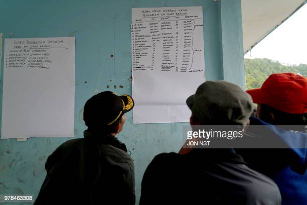 Family members look at a survivor list at the Lake Toba ferry port in the province of North Sumatra on June 19 after a boat capsized on June 18...