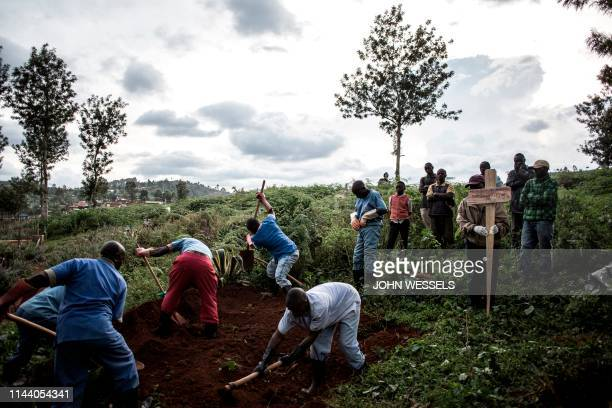 TOPSHOT Family members look on as they watch the deceased victim of the Ebola virus being buried on May 16 2019 in Butembo The city of Butembo is at...