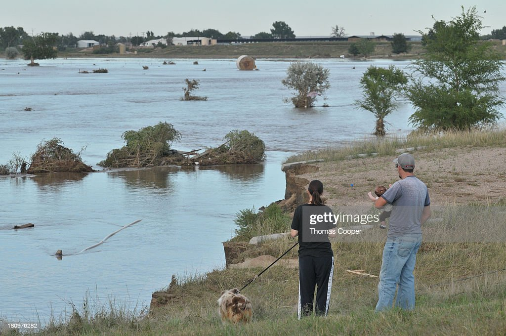 Family members look over a flooded field September 17, 2013 near Evans, in eastern Colorado. Even as flooding subsides, many in the hardest hit areas of the state remain stranded by washed out roads and rushing creeks and without water and power.