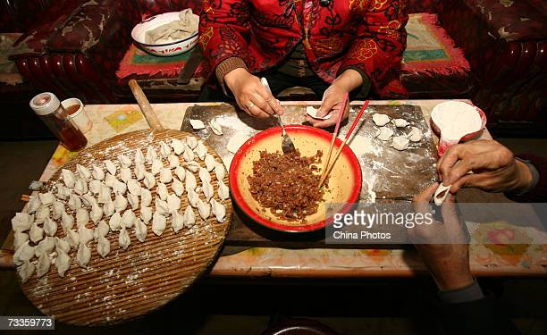 Family members make 'jiaozi' for dinner on the Chinese New Year's Eve in the village of Yangxi on February 17 2007 in Fuxian County of Shaanxi...