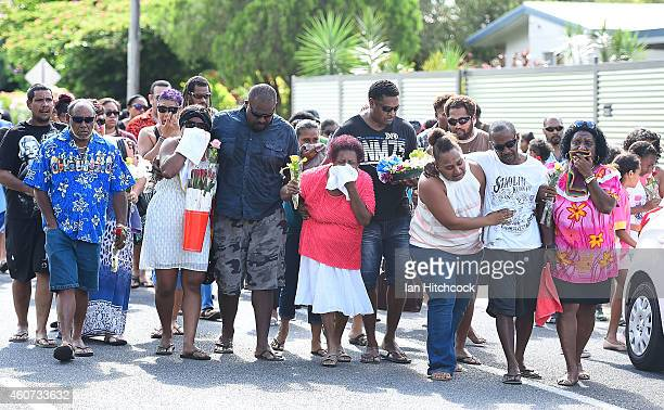 Family members mourn as they walk to a memorial which is located in the park next the home of a multiple stabbing in the suburb of Manoora on...