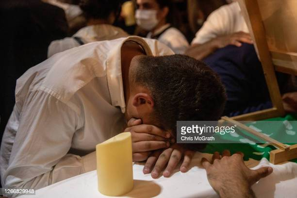 Family members mourn at a church service for firefighters Charbel Hetti, Najeeb Hetti and Charbel Karem who were killed in the August 4th, Beirut...