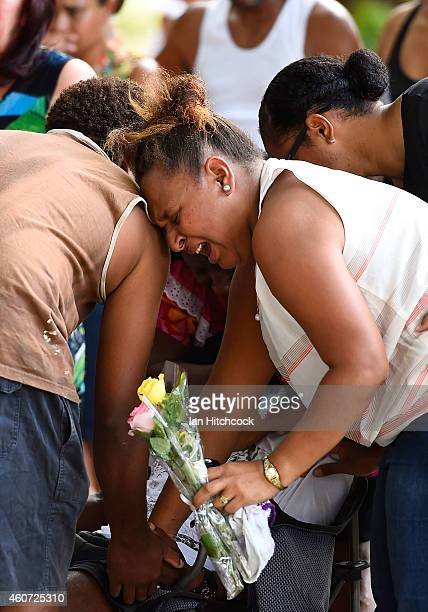 Family members mourn at the scene of a memorial which is located in the park next the home of a multiple stabbing in the suburb of Manoora on...