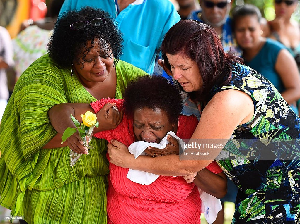 Family members mourn at the scene of a memorial which is located in the park next the home of a multiple stabbing in the suburb of Manoora on December 21, 2014 in Cairns, Australia. Eight children have been found dead and a 37-year-old woman is in hospital with chest injuries at a home in North Queensland. The children, aged 18 months to 14 years have reportedly been stabbed and the woman has been arrested for murder.