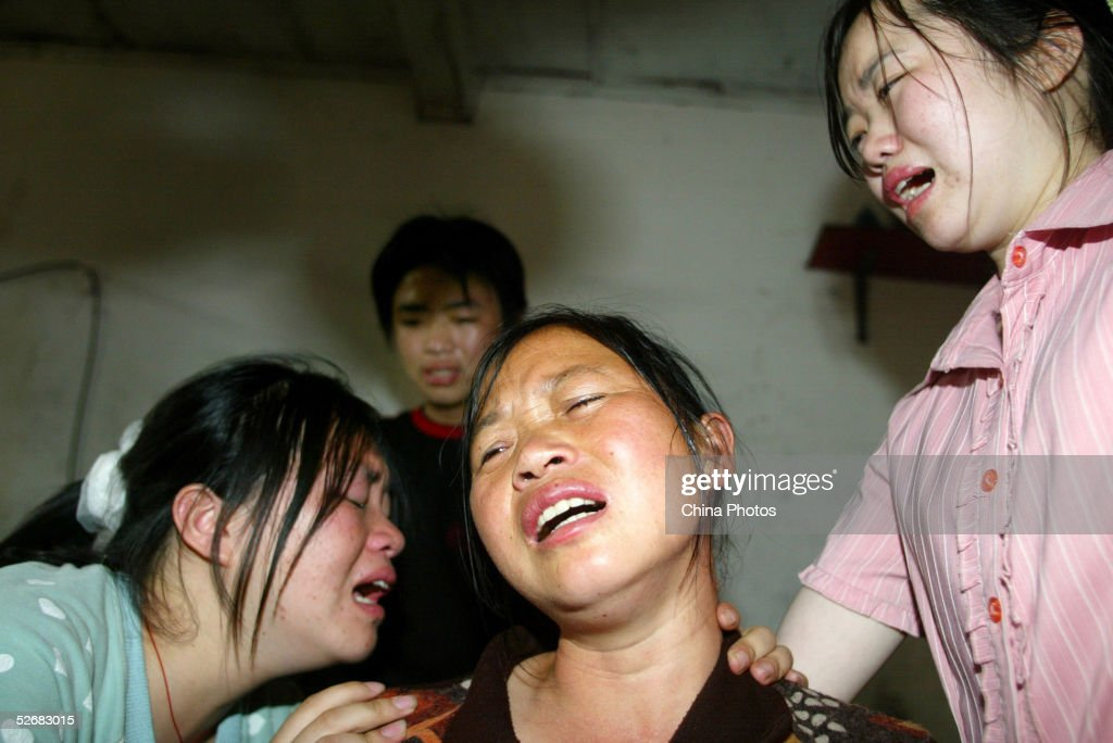 Family members mourn Chinese man Zuo Wenguang who died as he tried to rescue poisoned workers at a pickle processing factory on April 22, 2005 in Guangzhou of Guangdong Province, China. Zuo Wenguang, 51, a resident living near the factory, was killed by sulfureted hydrogen gas when he tried to save poisoned workers. Four workers had fainted at a fermenting pool while cleaning it April 21 and Zuo rushed to save the victims dieing after carrying two workers to safety. The accident has killed three people including Zuo and two workers.