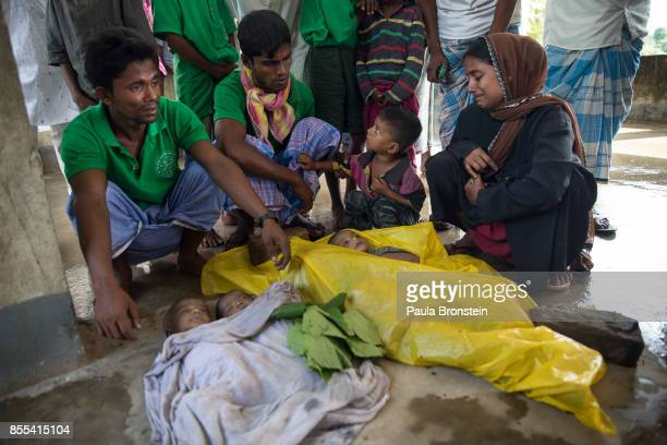 Family members mourn next to the bodies of babies before the funeral after a boat sunk in rough seas off the coast of Bangladesh carrying over 100...