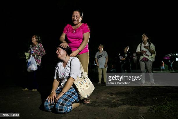Family members mourn the death of two of their daughters as they weep outside of the school dormitory where a fire broke out on Sunday night killing...