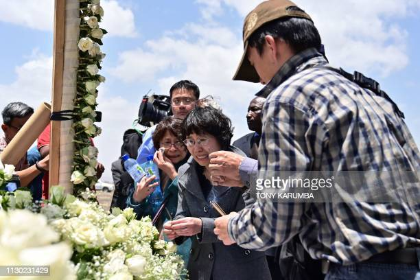 TOPSHOT Family members mourn the victims as they light incense at the crash site of the Ethiopian Airlines operated Boeing 737 MAX aircraft at Hama...