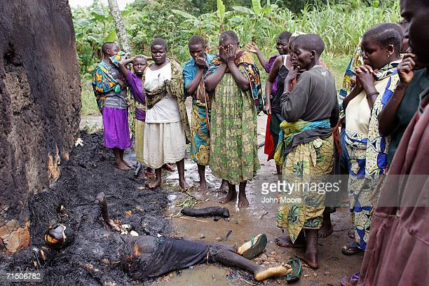 Family members mourn while seeing the charred bodies of loved ones on the outskirts of the Gety camp for displaced people July 23 2006 in the Ituri...