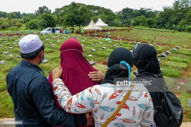 Family members of a victim of the COVID-19 coronavirus mourn during a funeral in Jakarta on March 31, 2020.