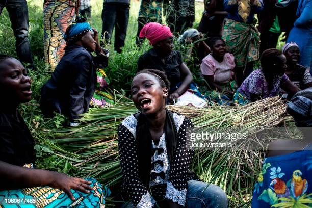 Family members of a woman killed in an alleged attack by the Ugandan Allied Democratic Forces rebel group react as the coffin is buried on November...