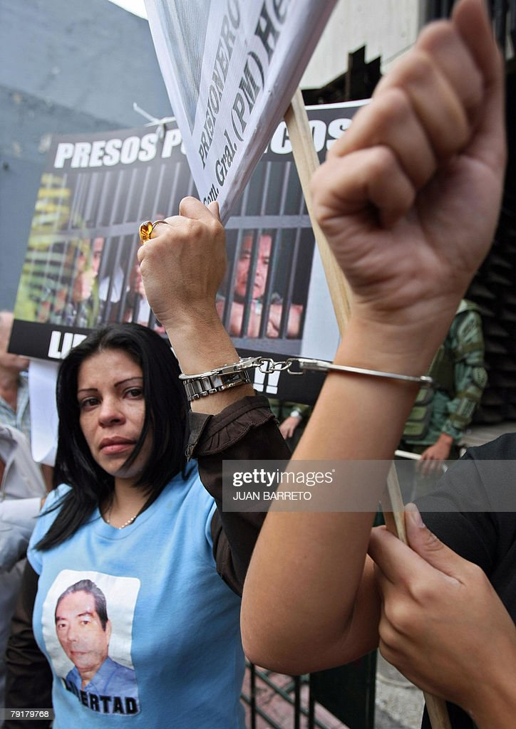 Family members of alleged political prisoners protest with handcuffs during a demonstration against Venezuelan president Hugo Chavez 23 January, 2008 in Caracas. The Venezuelan government commemorated today the 50th anniversary of the fall of the last dictatorship -gen. Marcos Perez Jimenez (1948-58). AFP PHOTO/Juan BARRETO