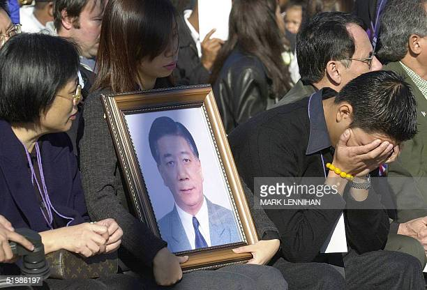 Family members of David Chen a victim of the crash of American Airlines Flight 587 attend a memorial service 18 November at Riis Park in the Queens...