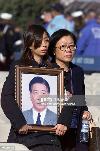 Family members of David Chen who was killed in the crash of American Airlines Flight 587 hold his photograph during a seaside prayer service for the...