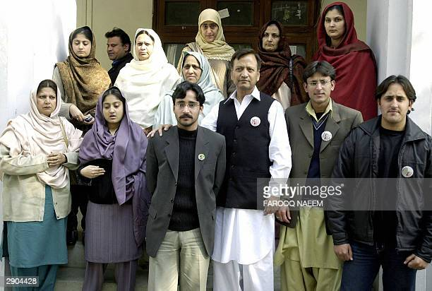 Family members of detained Pakistani nuclear scientists and officials pose for photographers while leaving a court in Rawalpindi 27 January 2004...