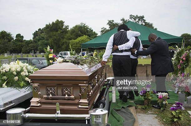 Family members of Emanuel AME Church shooting victim Ethel Lance are helped away during her burial at the Emanuel AME Church Cemetery in Charleston...
