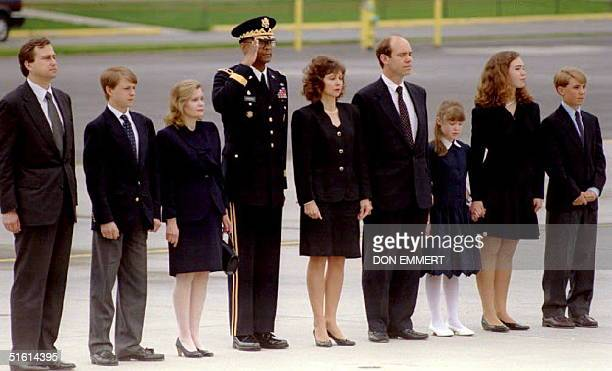 Family members of former President Richard Nixon are joined by a military representative as Nixon's body is loaded onto a plane 26 April 1994 at...
