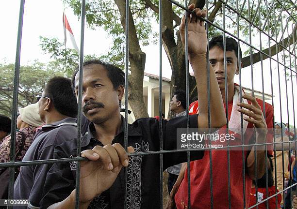 Family members of Indonesians who have returned from overseas some forcibly wait for their loved ones outside the restricted area at an immigration...