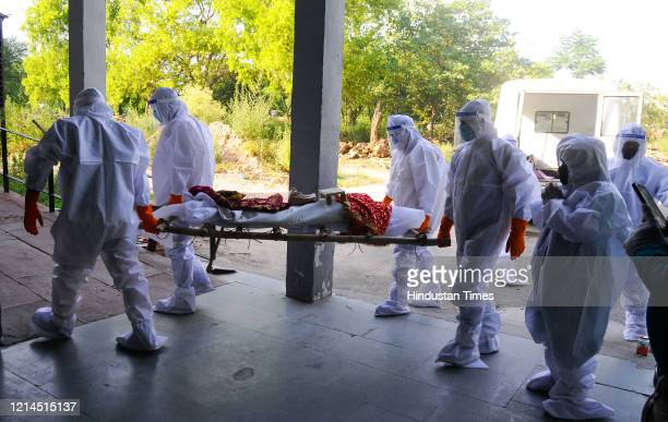 Family members of late Asha Rani, who died of Covid-19 infection carry her mortal remains for a funeral, in LPG Crematorium, Sector 25, on May 19,...