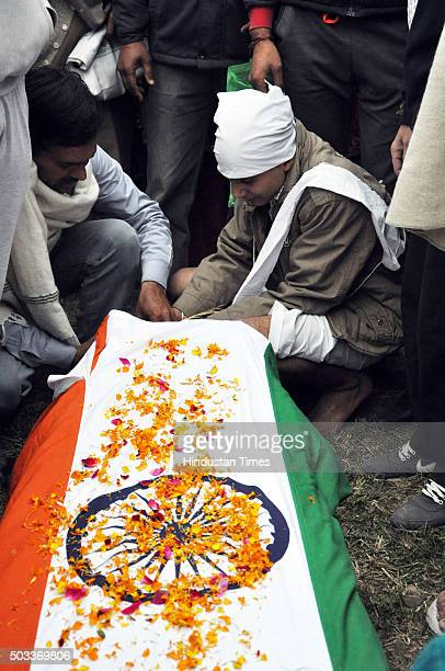 Family members of martyred soldier Havildar Jagdish Chand who lost his life while fighting terrorists in Pathankot wail near his body during his...