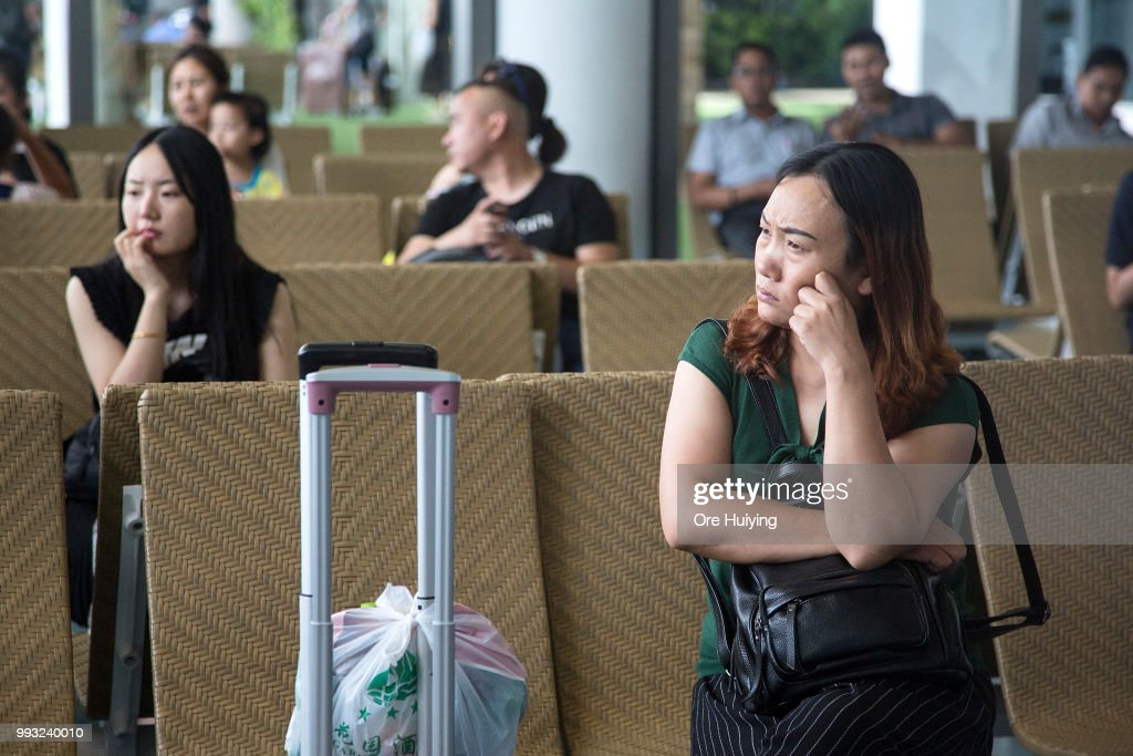 Family members of passengers onboard a capsized tourist boat wait at Phuket Airport upon their arrival on July 7, 2018 in Phuket, Thailand. At least 33 people drowned and another 23 are missing after a tourist boat carrying mostly Chinese passengers capsized off the holiday island of Phuket in southern Thailand. The boat carried 105 people, including 93 tourists, 11 crew and one tour guide, and went down during severe weather on Thursday evening as authorities announced all of the dead are Chinese nationals.