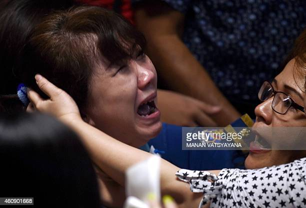 Family members of passengers onboard the missing Malaysian air carrier AirAsia flight QZ8501 react after watching news reports showing an...