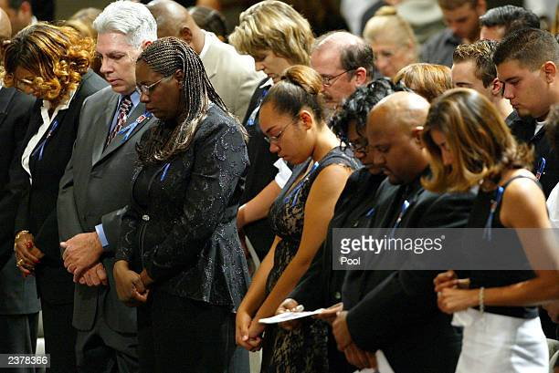 Family members of Patrick James Dennehy bow their heads in prayer during his memorial service August 7 2003 at the Jubilee Christian Center in San...