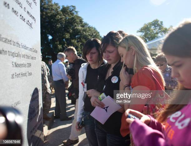 Family members of Pfc. Aaron Nemelka recognize his service on the memorial stone during a memorial service recognizing victims and families of those...