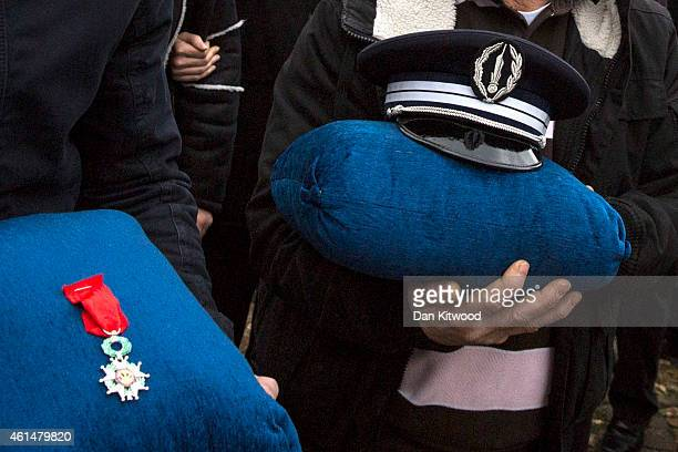 Family members of police officer Ahmed Merabet hold his cap and his Legion of Honor decoration during his funeral at a muslim cemetery on January 13...