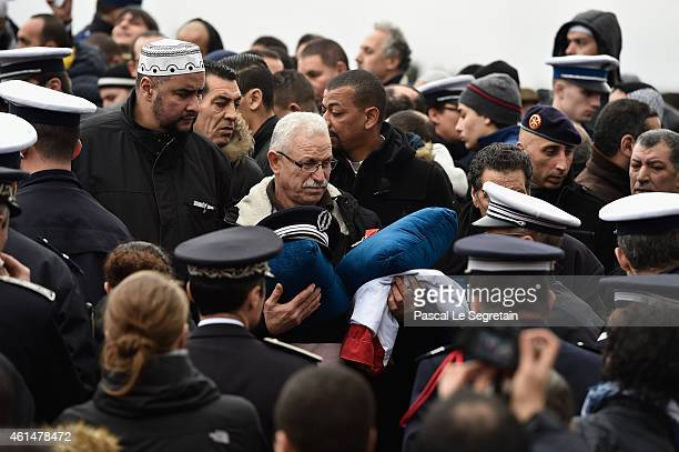 Family members of police officer Ahmed Merabet, hold his cap, his Legion of Honnor decoration and French flag during a funeral at a muslim cemetary...