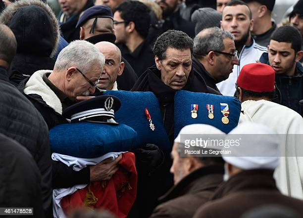 Family members of police officer Ahmed Merabet, hold his cap, his Legion of Honnor decoration and the French flag during his funeral at a muslim...