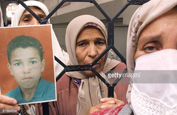 Family members of several people massacred in the recent armed terrorist attacks display 19 January 2001 in Algiers photographs of their relatives...