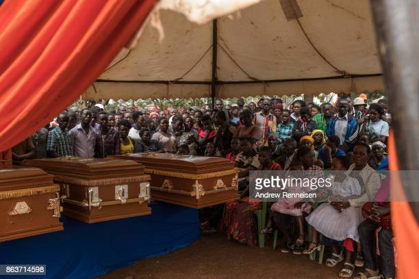 Family members of the deceased sit with the caskets during the funeral of three men killed by the police in an opposition protest the week prior on...