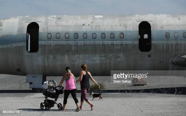 Family members of United Nations peacekeepers jog past a decaying and abandoned passenger plane of Cyprus Airways at Nicosia International Airport...
