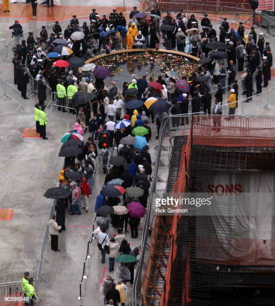Family members of victims firefighters and police officers walk in line in the rain at the reflecting pool placing flowers as people gather at Ground...