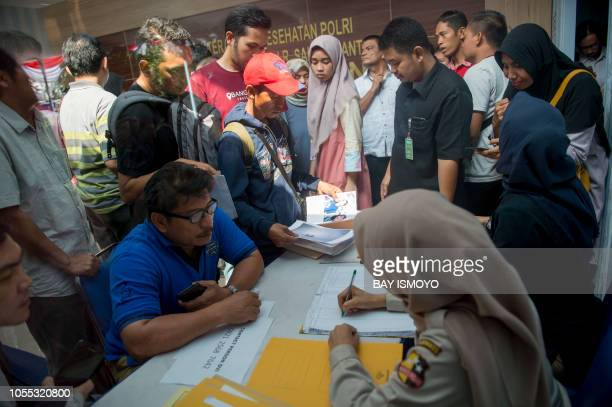 Family members of victims of the illfated Lion Air flight JT 610 submit papers and photographs of their lost relatives at a disaster victim...