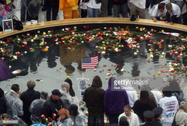 Family members of victims stand in the rain at the reflecting pool placing flowers as people gather at Ground Zero during a 9/11 memorial ceremony on...