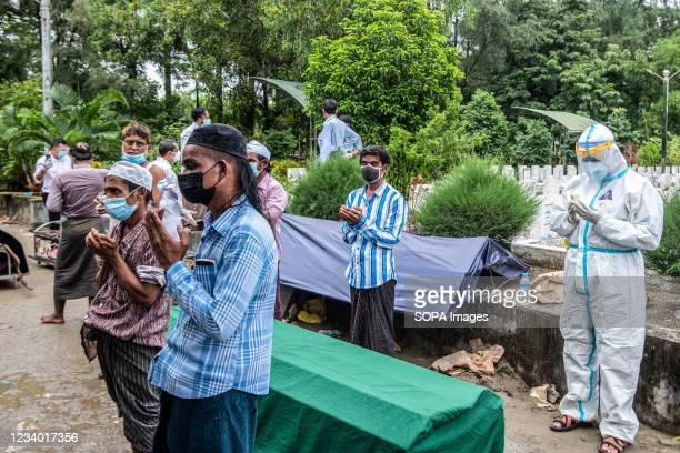Family members offer prayers for their deceased relative who died due to the COVID-19 coronavirus at a graveyard. The Muslim community of Yangon...