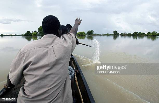 Family members paddle a canoe across their inundated fieldsd 23 September 2007 near the village of Nasia in northern Ghana after the Volta Blanc...