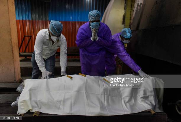 Family members pay their respects to a relative who died due to coronavirus before their body enters a furnace for cremation at Nigambodh Ghat...