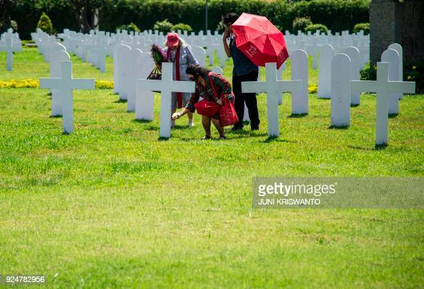 Family members pay their respects to the 915 Dutch soldiers killed in the battle of the Java Sea at the Dutch war cemetery Ereveld in Surabaya on...