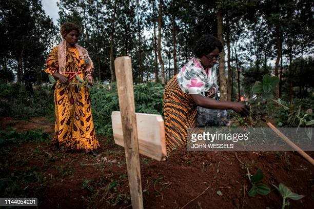 Family members place leaves on the grave of a deceased Ebola virus victim being during their funeral on May 16, 2019 in Butembo. - The city of...