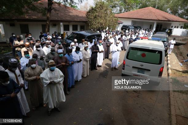 Family members pray as an ambulance carrying the body of Nigerias Chief of Staff Abba Kyari pass by in Abuja on April 18 2020 Abba Kyari the chief of...