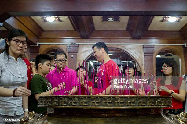 Family members put their incense in a golden pot located at the center of the shrine after praying