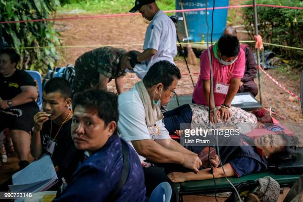 Family members rescue staffs receive traditional massage therapy at a makeshift camp at Khun Nam Nang Non Forest Park to follow up with the rescue...