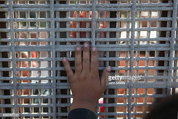 Family members reunite through bars and mesh of the USMexico border fence at Friendship Park on November 17 2013 in San Diego California The US...