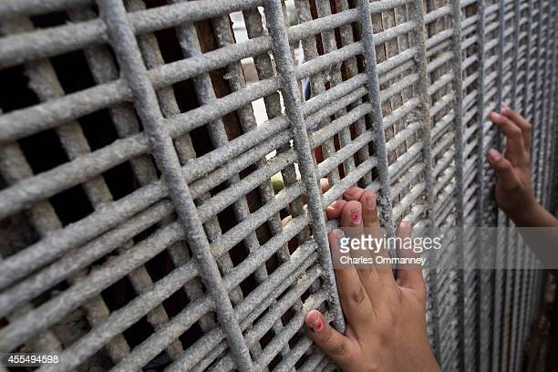 Family members reunite through bars and mesh of the USMexico border fence at Friendship Park on January 26 2014 in San Diego California The US Border...