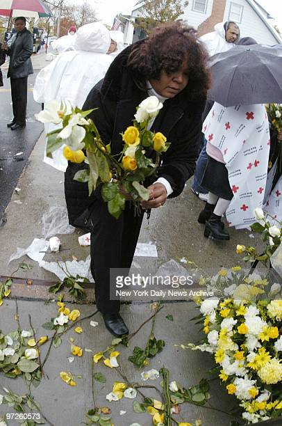 Family members scatter yellow and white flowers in remembrance of their loved ones during a rainy memorial service at Newport Ave and Beach 131st St...